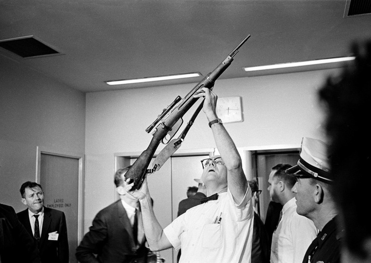 Police Lt. J.C. Day holds aloft the bolt-action rifle with telescopic sight which was allegedly used in the assassination of U.S. President John F. Kennedy, Dallas, Texas, on Nov. 22, 1963