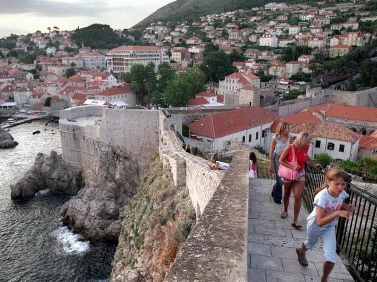Tourists walk on the city wall that rings the historic town of Dubrovnik, Croatia.