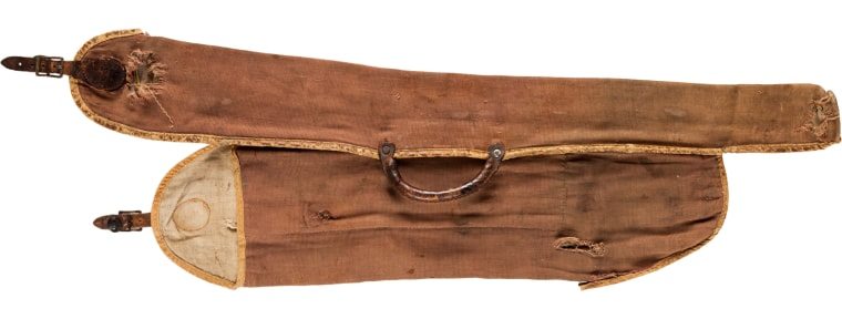 A canvas field scabbard with two sleeves, one fitted for the barrels and one for the receiver and stock of the 16-gauge Parker Brothers Hammer shotgun once owned by Old West trick shooter Annie Oakley.