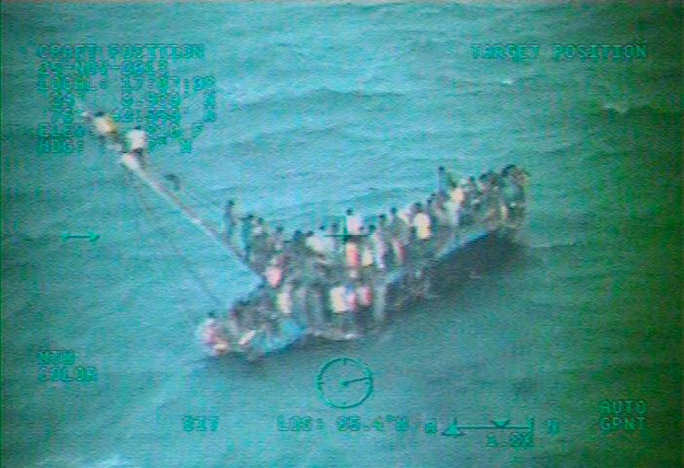 Approximately 100 Haitians sit on the hull of a sail freighter after it grounded and capsized 15 nautical miles southwest of Staniel Cay, Bahamas, on Tuesday. At least 10 Haitian migrants were killed and about 100 more were clinging to the hull of an overloaded freighter that capsized in the Bahamas, the U.S. Coast Guard said on Tuesday.