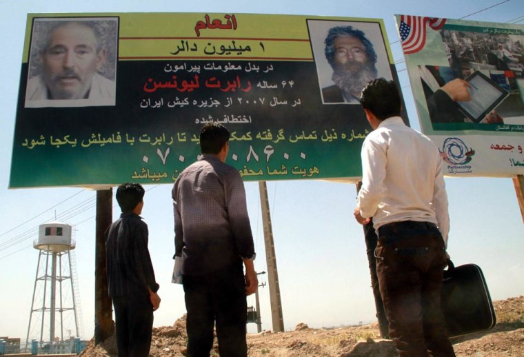 Afghans look at a billboard promising a reward for information leading to the recovery of former FBI agent Robert Levinson, in Herat, near the Iranian border, on April 24, 2012.