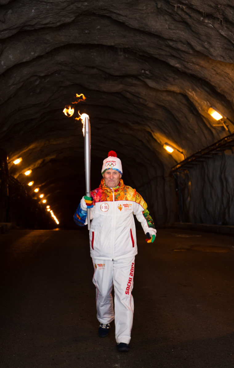 Nikolai Malykh carries the torch during the Olympic flame relay in a tunnel of a Siberian hydroelectric plant this week. Another torchbearer briefly caught fire.