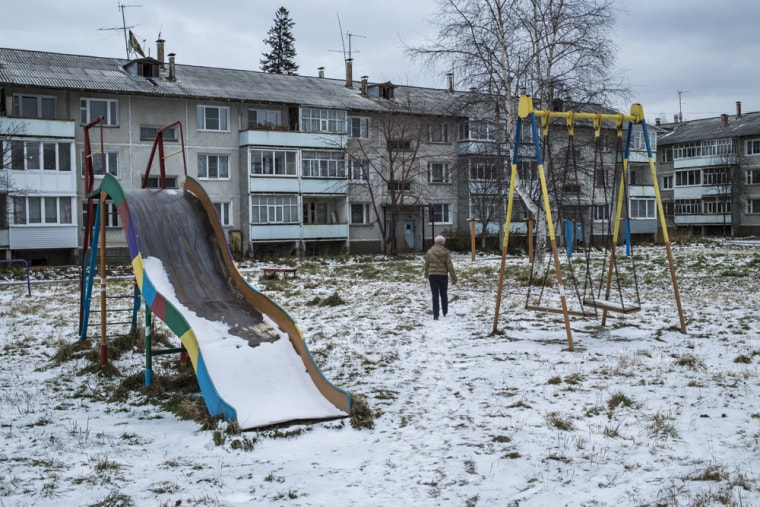 A woman walks through a playground outside a block of apartments in Baikalsk, Russia. The local economy has been devastated by the recent bankruptcy of the Siberian town's only major employer -- a pulp and paper mill which for decades polluted Lake Baikal.