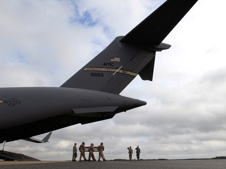 A Marine carry team carries the transfer case containing the remains of Marine Lance Cpl. Jeremiah M. Collins Jr. of Milwaukee, upon arrival at Dover ...