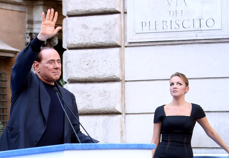 Former Prime Minister Silvio Berlusconi, flanked by his new girlfriend Francesca Pascale, waves to his supporters during a Pro-Berlusconi rally outside his Rome residence, Palazzo Grazioli at Via del Plebiscito, on August 4, 2013.