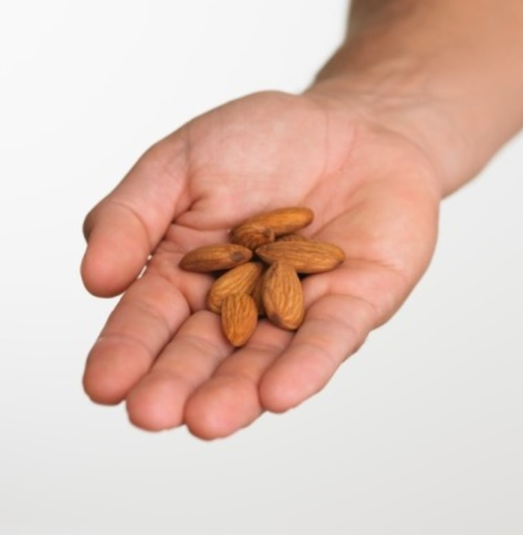 Close up studio shot of man holding almonds