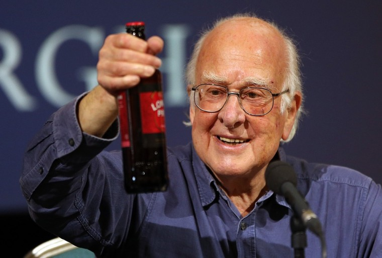 Nobel-winning physicist Peter Higgs holds up a celebratory bottle of London Pride beer at a press conference at the University of Edinburgh on Friday.