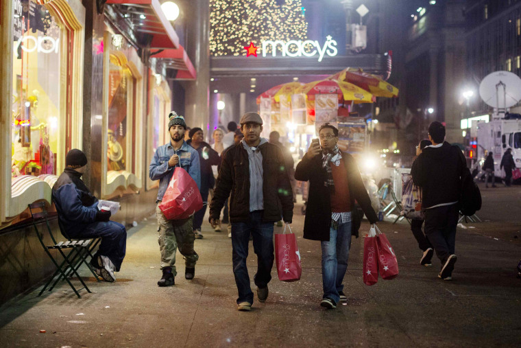 Shoppers carry bags as they leave Macy's in New York in this Nov. 23, 2012, file photo. This year, Macy's said it will open most of its stores on Thanksgiving for the first time.