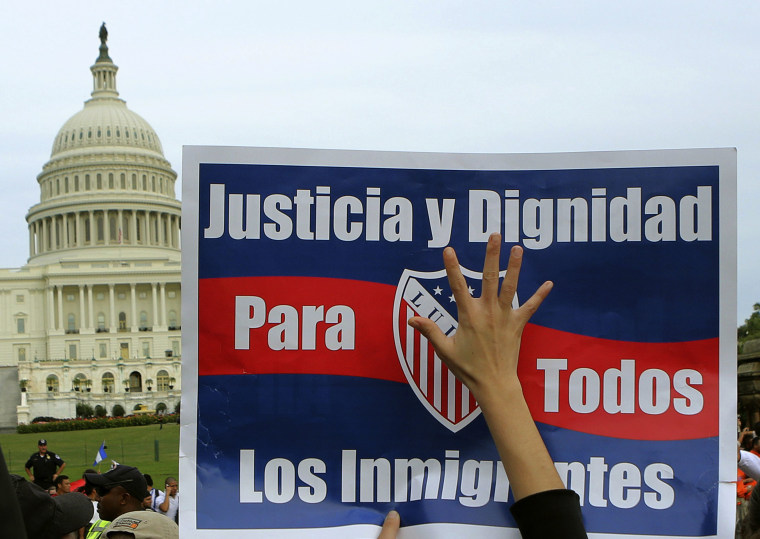 A woman holds up a sign during a protest rally for immigrants rights on Capitol Hill in Washington October 8, 2013. The sign reads