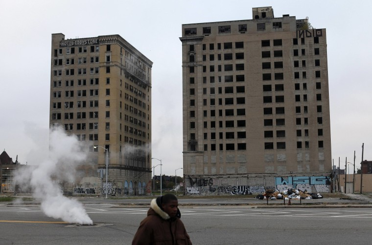 A man walks past two abandoned buildings in Detroit on Friday, Oct. 25, the third day of a trial to determine whether the city is eligible for bankruptcy.
