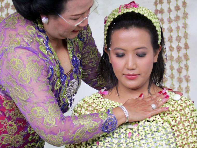Yogyakarta Sultan Hamengkubuwono X's fourth daughter Princess Hayu, 29, covered with a cape of flowers is bathed with water during a purification ritu...