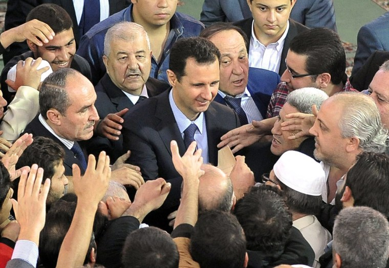 Syrian President Bashar al-Assad being greeted by supporters following Eid al-Adha prayers at the Sayeda Hassiba mosque in Damascus' northwestern Dumar neighborhood on October 15, 2013.