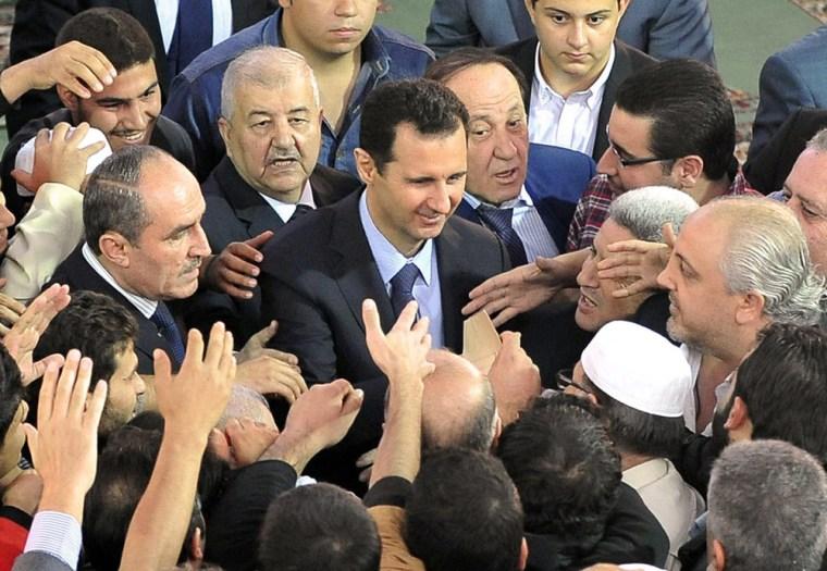 Syrian President Bashar al-Assad being greeted by supporters following Eid al-Adha prayers at the Sayeda Hassiba mosque in Damascus' northwestern Dumar neighborhood on October 15, 2013.