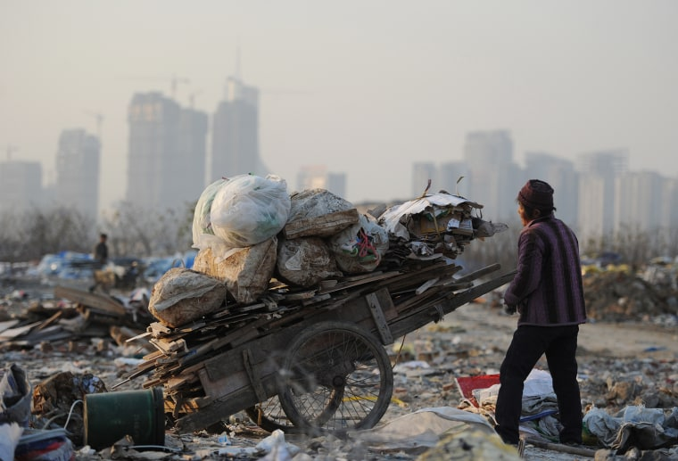 This picture taken on December 9, 2012 shows scavengers picking up useful construction waste from a garbage dump in Hefei, central China's Anhui provi...