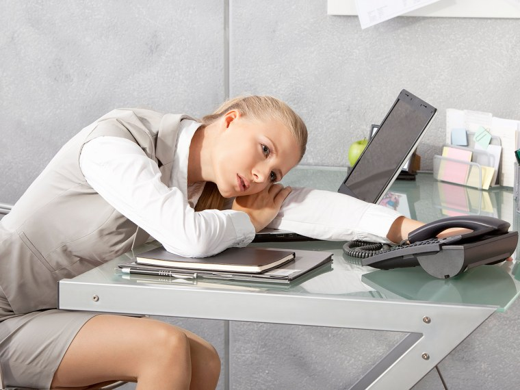 Young woman sitting tired at desk