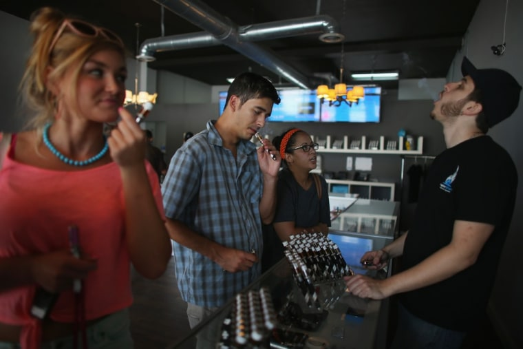Jonathan Gonzalez (2nd L) and Yanci Gonzalez with Eric Arnau, at the Vapor Shark store in Miami. A study has found e-cigarettes may help people quit smoking tobacco.