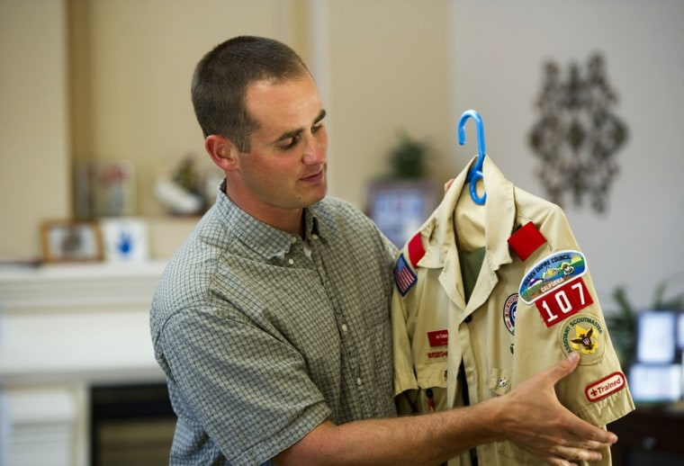 Jonathan Pickens looks at his boy scouts uniform which badges and patches he earned as a boy at his home in Roseville, California, Thursday, September 5, 2013.
