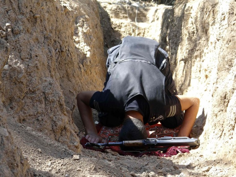 A Free Syrian Army fighter prays near a weapon in a trench in Al-Maliha, in the Damascus suburbs, on Monday.