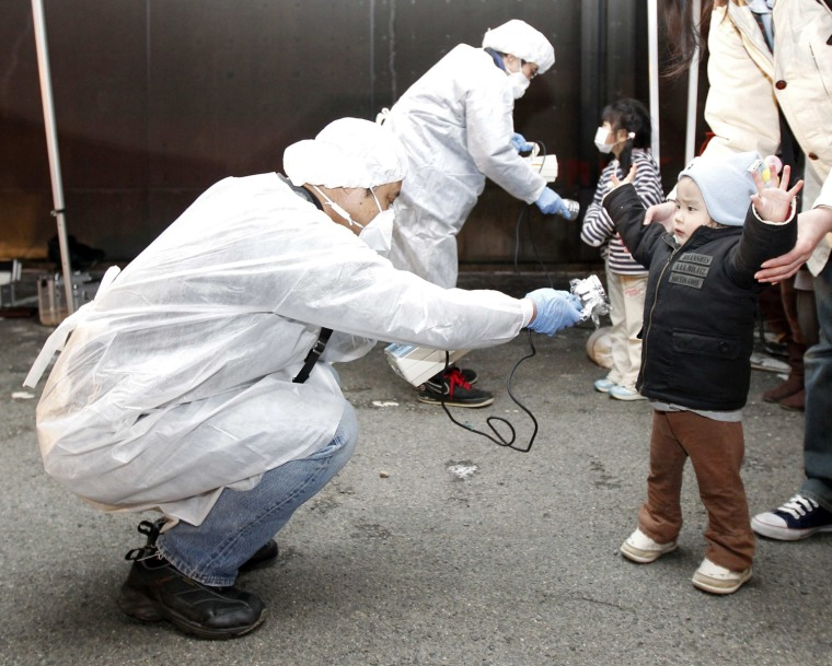 Officials in protective gear check for signs of radiation on children who are from the evacuation area near the Fukushima Daini nuclear plant in Koriyama, in March 2011.