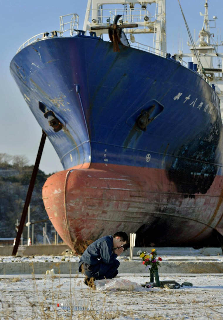 A man prays as he mourns victims of the 2011 earthquake and tsunami as a ship brought ashore by the disaster is seen in the background, in Kesennuma, Japan, in March this year.