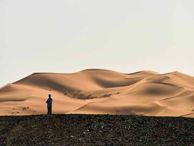 A man on Sand Dunes. Sahara Desert near Merzouga, Morocco, North Africa, Africa. Photo by: Frank May/picture-alliance/dpa/AP Images