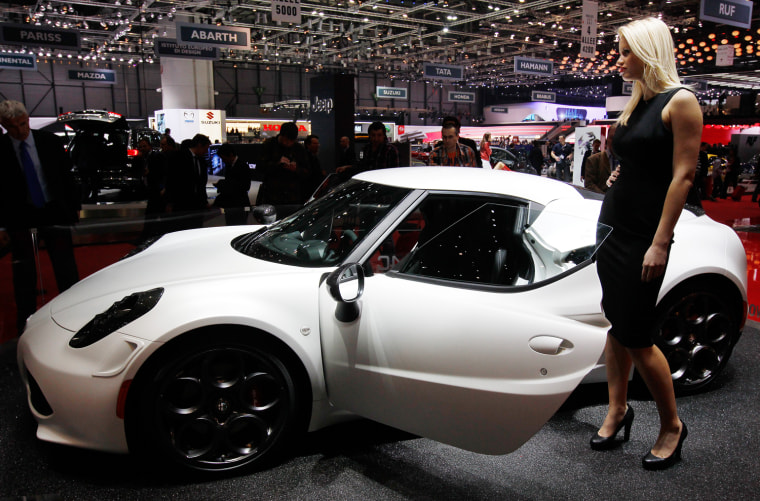 A model stands next to the Alfa Romeo 4C displayed on the company's booth during the first media day of the Geneva Auto Show at the Palexpo in Geneva ...