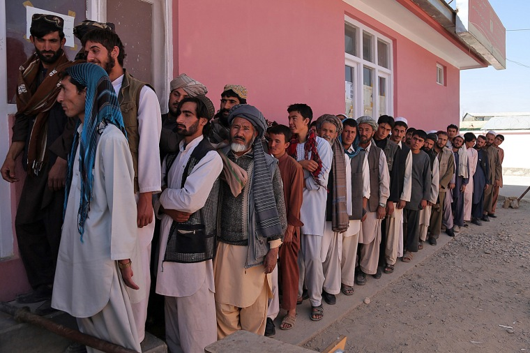 Afghan men wait to receive their identification cards to vote in upcoming elections at a registration center in Ghazni on Sept. 17, 2013.