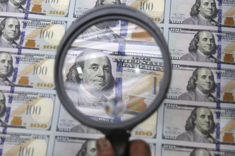 A sheet of uncut $100 bills is inspected during the printing process at the Bureau of Engraving and Printing Western Currency Facility in Fort Worth, ...