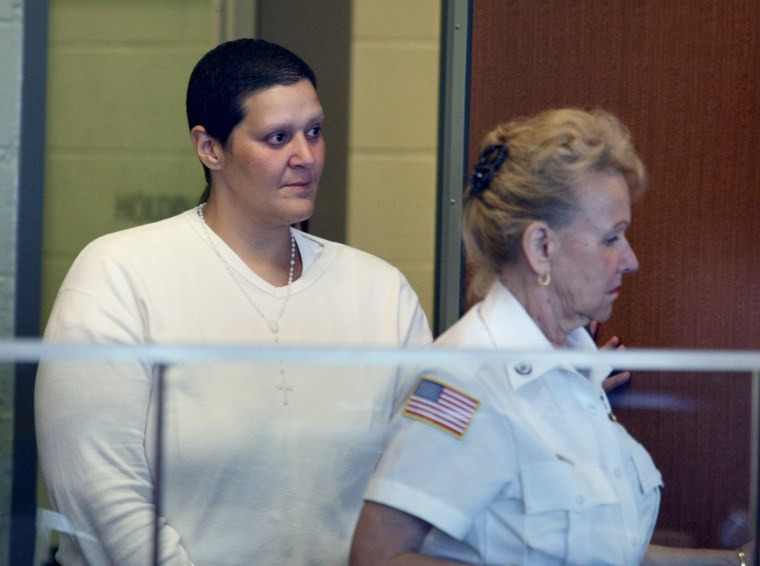 Tanya Singleton, a cousin of former New England Patriots player Aaron Hernandez, is escorted into Superior Court in Fall River, Mass. Friday, Aug. 23, 2013 where she pleaded not guilty on a contempt charge for allegedly refusing to testify before the grand jury that indicted Hernandez in the murder of 27-year-old Odin Lloyd. (AP Photo/Boston Globe,George Rizer, Pool)