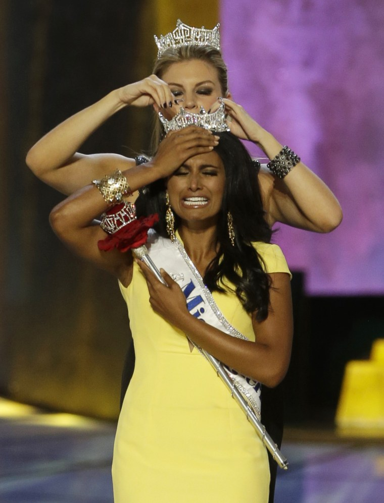 Miss New York Nina Davuluri, front, is crowned as Miss America 2014 by Miss America 2013 Mallory Hagan, Sunday, Sept. 15, 2013, in Atlantic City, N.J....