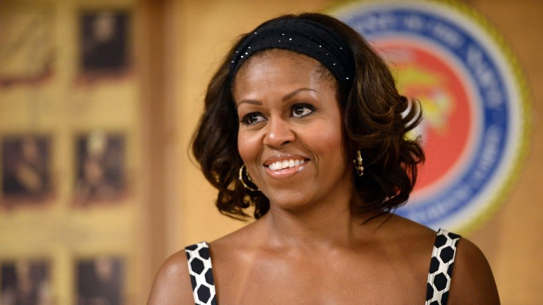 US First Lady Michelle Obama smiles as  President Barack Obama talks to members of the military and their families during a Christmas dinner in Anders...