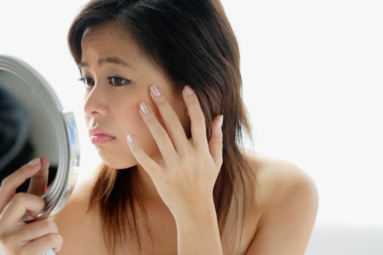 Image: Young woman looking at mirror