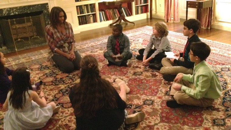 """First Lady Michelle Obama sits with """"kid reporters"""" at the White House to talk about her """"Let's Move!"""" initiative."""