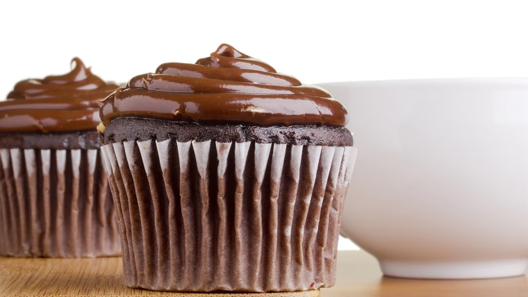 Decorated chocolate cupcake next to a white cup.