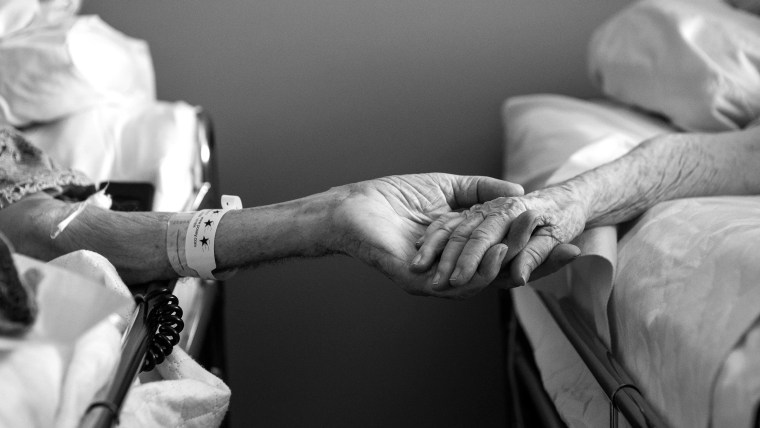 In this July, 2014 photo provided by their granddaughter Melissa Stone, Don Simpson, 90, and his wife Maxine, 87, hold hands from adjoining hospice be...