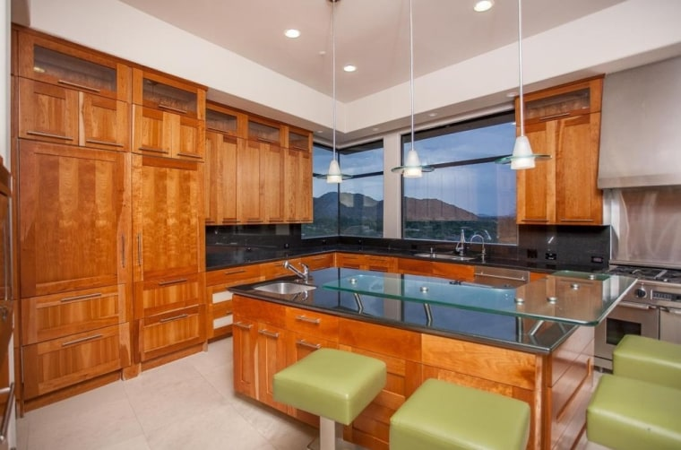 The gourmet kitchen features cherry wood, granite and glass.