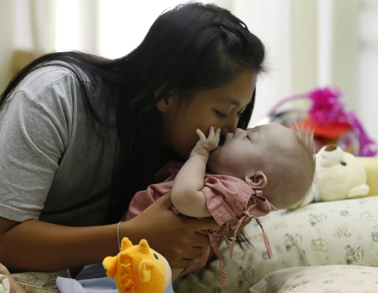 epa04340343 A Thai surrogate mother, Pattharamon Janbua (L), 21, kisses her seven-month-old Down's Syndrome baby, Gammy or Naruebet Mincharoen at a ho...