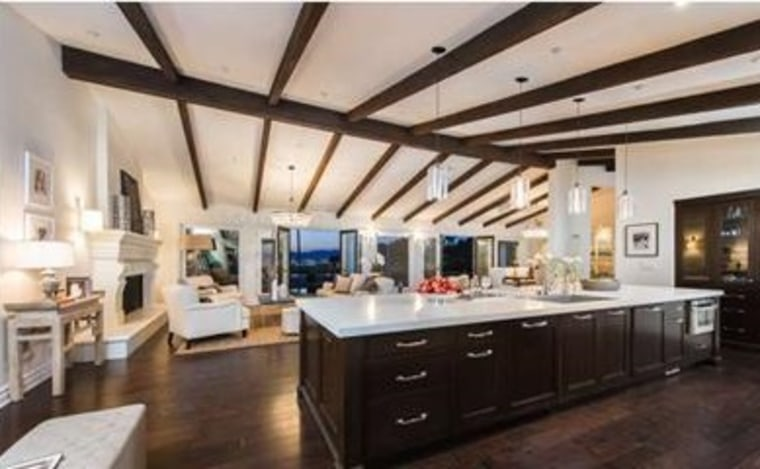 The home features beamed ceilings, hardwood floors and an open floor plan.