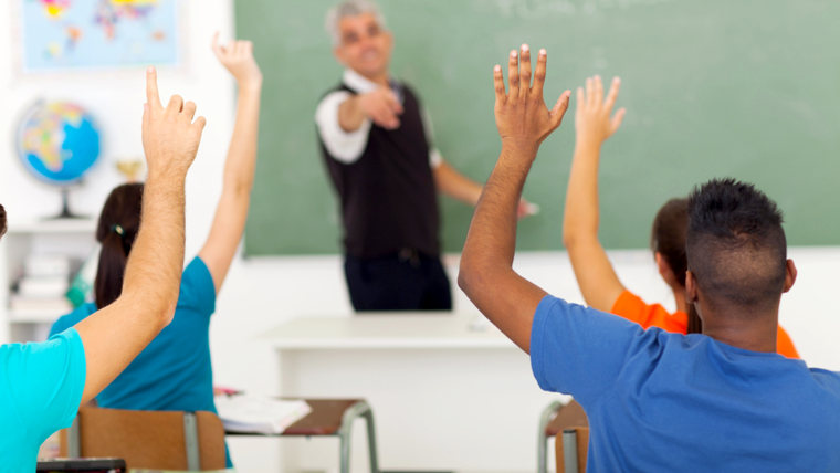 group of students with hands up in classroom during a lesson; Shutterstock ID 141891325; PO: today.com