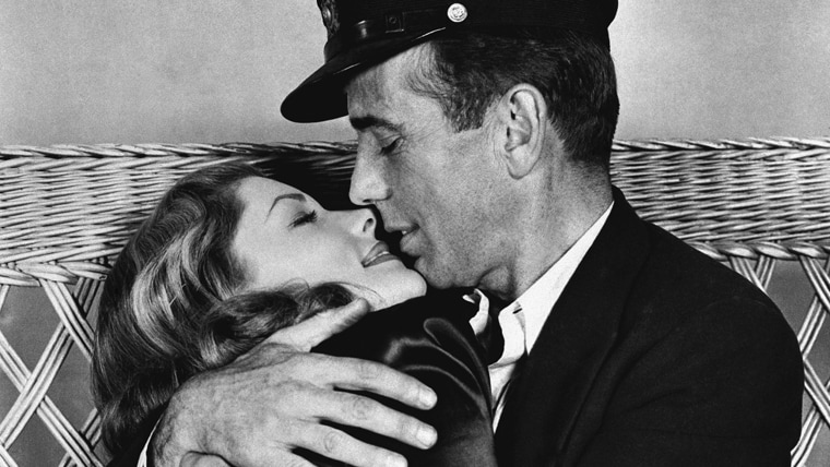 "Image: Actor Humphrey Bogart holds actress Lauren Bacall in a tight embrace in their latest film ""To Have and Have Not"""