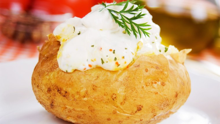 Baked potato with sour cream sauce, selective focus