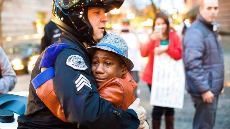Portland police Sgt. Bret Barnum, left, and Devonte Hart, 12, hug at a Ferguson protest rally in Portland, Oregon, on Nov. 25.