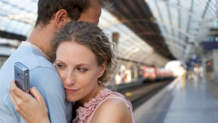 Couple embracing on station platform, woman looking at mobile phone, Separation, Horizontal, Waist Up, Indoors, Side View, Mobile Phone, Caucasian App...