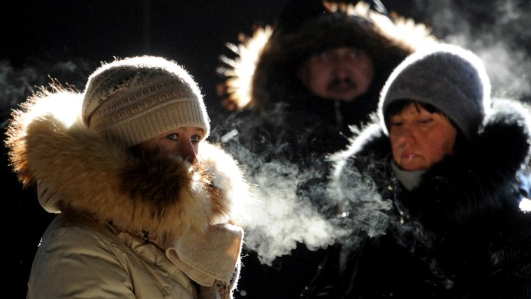 Women's frozen breath hangs in the air in central Minsk, on January 30, 2014. The temperatures in the Belarus capital dropped today to - 18 C, but due...