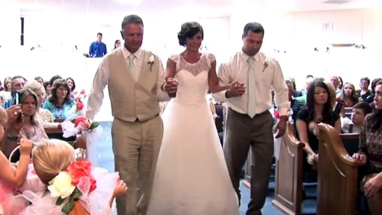 Katie Hughes walks down the aisle with her father, to her right, and her trainer.