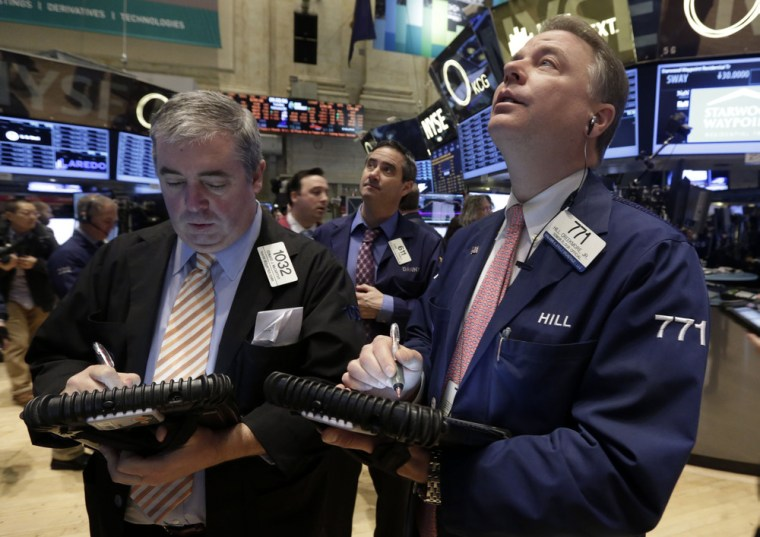 Trader Edward McCarthy, left, and F. Hill Creekmore, right, work on the floor of the New York Stock Exchange Tuesday, Feb. 4, 2014. Stocks are mixed o...