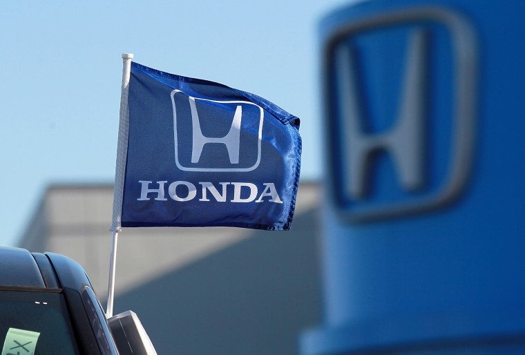 SAN RAFAEL, CA - DECEMBER 02: A flag with the Honda logo is displayed on brand new Honda car at Marin Honda on December 2, 2011 in San Rafael, Califo...