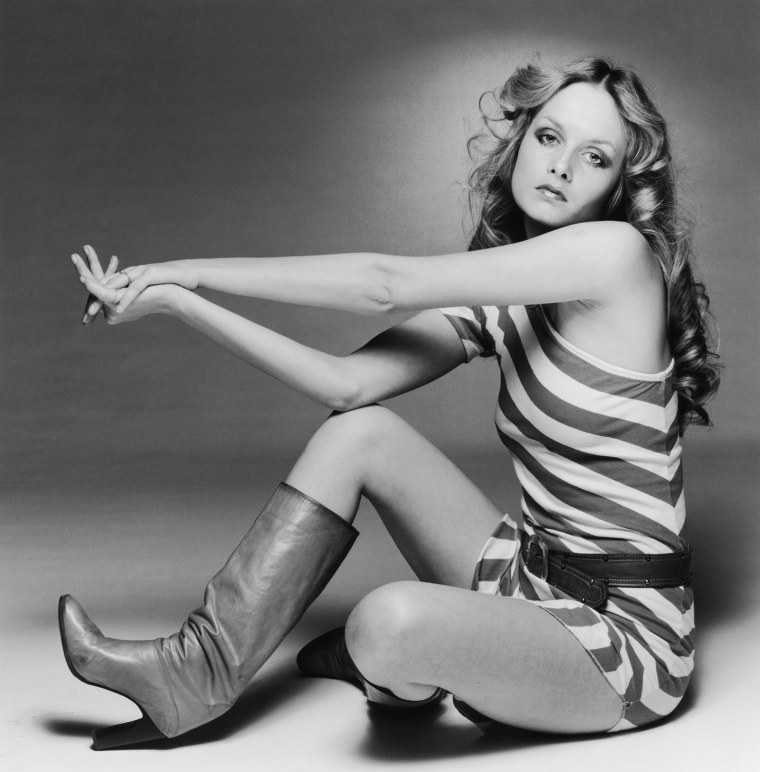 British model Twiggy, born Leslie Hornby, wearing a short striped outfit with knee length boots, early 1970s. (Photo by Terry O'Neill/Getty Images)