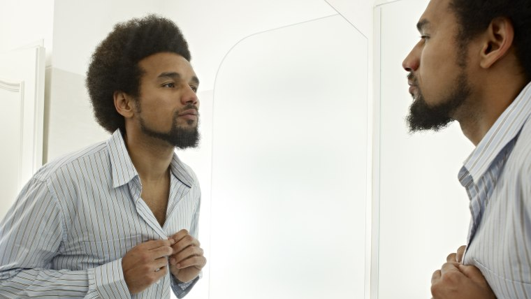 Young man dressing in front of mirror