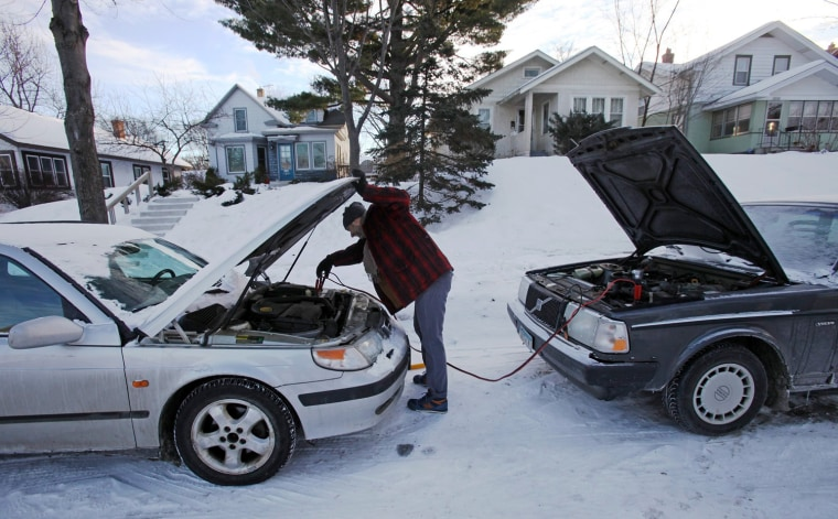 James Diers unhooks jumper cables after he was unable to jump start his car in Minneapolis, Jan. 7, 2014. The Arctic air that has gripped much of the country could cost us $5 billion.
